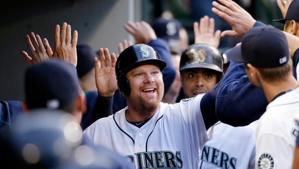Seattle Mariners' Adam Lind smiles as he is greeted