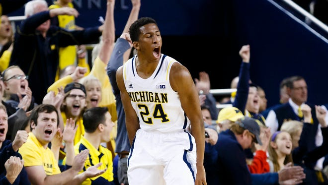 Michigan guard/forward Aubrey Dawkins celebrates a three-point basket in overtime against the Illinois Fighting Illini at Crisler Center. Michigan won 73-65 in overtime.