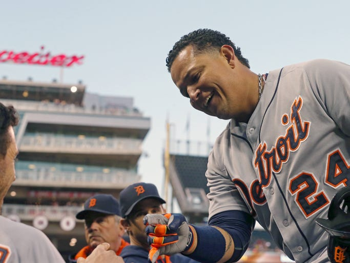 Detroit Tigers' Miguel Cabrera is greeted at the dugout after scoring on a double by Victor Martinez off Minnesota Twins pitcher Anthony Swarzak in the first inning of their game, Monday, Sept. 15, 2014, in Minneapolis. The Tigers won 8-6.