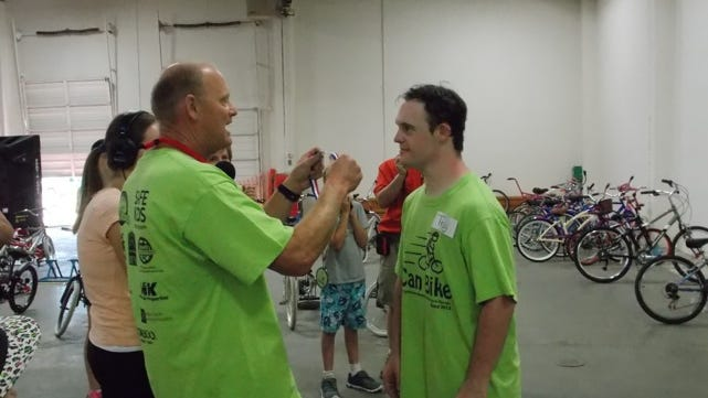 Troy Drake receives a medal from iCan Bike Camp volunteer Mark Smith after completing bicycle camp in which he was taught to ride a two-wheeled bike on his own. Troy, 24, has Down Syndrome and was never able to ride independently before the camp.