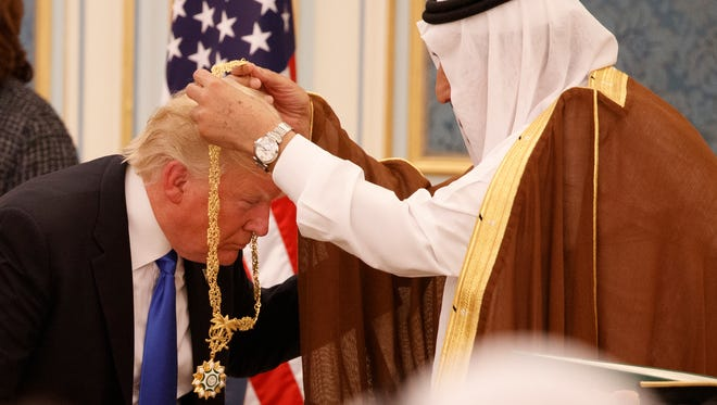 FILE -- In this Saturday, May 20, 2017 file photo, Saudi King Salman presents President Donald Trump with the highest civilian honor, the Collar of Abdulaziz Al Saud, at the Royal Court Palace, in Riyadh, Saudi Arabia. Trump had to bend down so the king could put the gold medal hanging from a long, gold chain around his neck, and that ignited debate over whether he had bowed to the king. (AP Photo/Evan Vucci, File)
