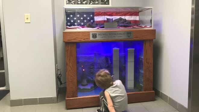 Blake Chapman, 4, of Belleville, examines a 9/11 memorial placed in the lobby at Town Hall in Belleville, built by members of Essex County's Second Chance Program for low-level offenders.