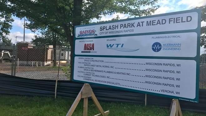 A sign for the splash park stands with the shelter and restroom building behind it at Mead Field in Wisconsin Rapids.