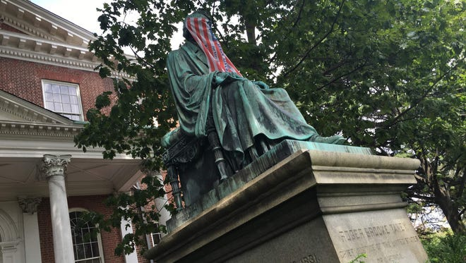 Roger B. Taney's statue is covered with a flag in Annapolis, Maryland.