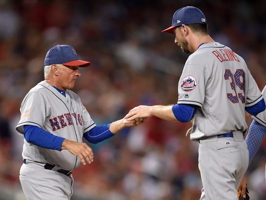 Mets manager Terry Collins, left, pulls relief pitcher