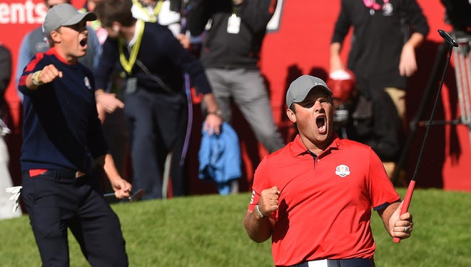 Patrick Reed celebrates after winning his match with Jordan Spieth against Europe's Justin Rose and Henrik Stenson  during the morning foursome matches at the 41st Ryder Cup at Hazeltine National Golf Course in Chaska, Minn.