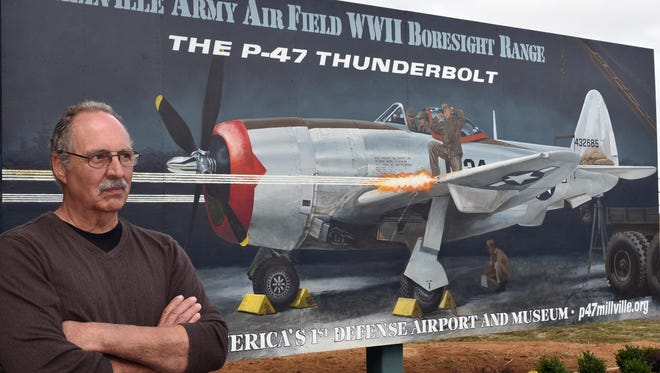 Artist Sam Donovan of Alloway stands next to a mural he painted that was unveiled at the at WW II boresight range inside the New Jersey Motorsports Park.