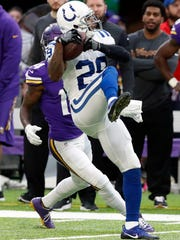 Indianapolis Colts safety Mike Adams, front, intercepts a pass as Minnesota Vikings wide receiver Stefon Diggs watches during the first half of an NFL football game Sunday, Dec. 18, 2016, in Minneapolis.