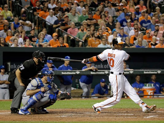 Baltimore Orioles' Adam Jones, right, doubles, in front of Kansas City Royals catcher Drew Butera and home plate umpire Jim Reynolds in the seventh inning of a baseball game in Baltimore, Monday, June 6, 2016. Nolan Reimold scored on the play, and Baltimore won 4-1. (AP Photo/Patrick Semansky)