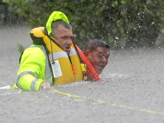 Wilford Martinez, right, is rescued from his flooded