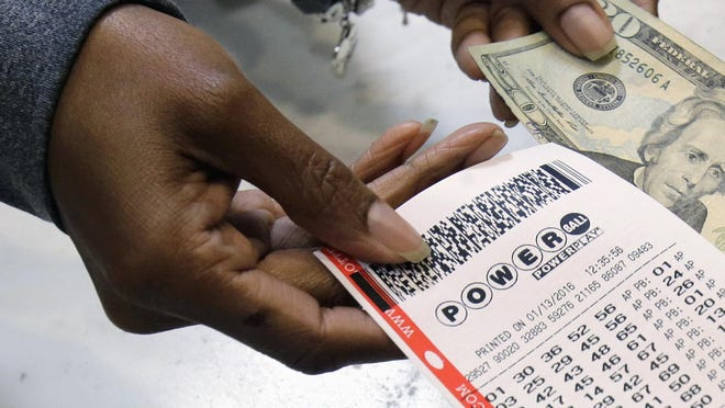 FILE - In this Jan. 13, 2016 file photo, a clerk hands over a Powerball ticket for cash at Tower City Lottery Stop in Cleveland. A ticket sold in Tennessee won more than $420 million in the Saturday, November 26 drawing. (AP Photo/Tony Dejak, File)
