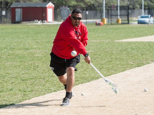 James M. Bennett lacrosse coach Milt Rodriguez shoots the ball at a goalie during a practice session on Tuesday, April 10, 2018.