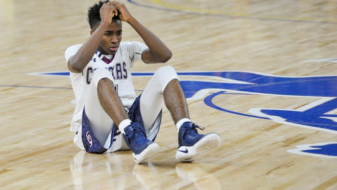 Jonathan Cissie sits in disbelief of losing by one point as St Thomas More takes on De La salle in the boys semi-final round of the state basketball championship in Burton Coliseum. Wednesday, March 8, 2017.