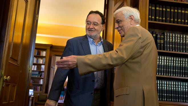 Former Energy Minister and head a party called Popular Unity , Panagiotis Lafazanis, left , is welcomed by Greek President Prokopis Pavlopoulos, in Athens, Monday Aug. 24, 2015.