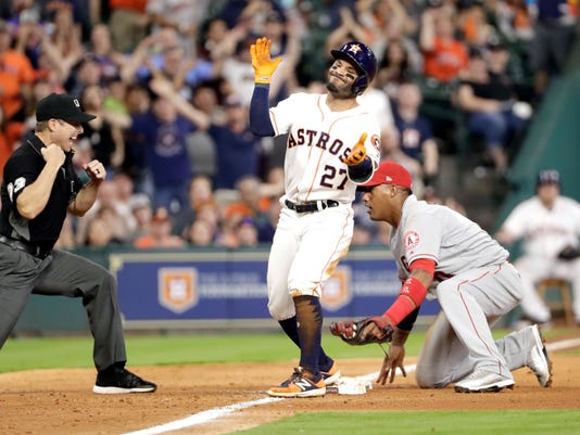 Houston Astros' Jose Altuve (27) reacts after being tagged out by Los Angeles Angels third baseman Yunel Escobar while trying to stretch a double into a triple during the eighth inning of a baseball game, Monday, April 17, 2017, in Houston. The Astros' Josh Reddick scored on the play. (AP Photo/David J. Phillip)