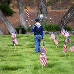 A Cub Scout from local pack 7322 helps to place flags on the gravestones of veterans at Our Mother of Sorrows Catholic Cemetery in Reno last year.