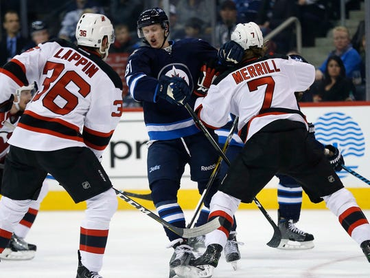 Winnipeg Jets' Kyle Connor (81) gets stopped by New Jersey Devils' Jon Merrill (7) and Nick Lappin (36) during the second period of an NHL hockey game Tuesday, Nov. 29, 2016, in Winnipeg, Manitoba. (John Woods/The Canadian Press via AP)
