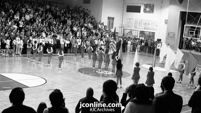 Here's a scene that probably never again will be repeated in Southwestern High School gymnasium. It was the playing of the national anthem for the last home game for the high school. Next fall Southwestern and Wainwright high schools will become McCutcheon High School. The present buildings will become junior highs. Disappearance of high school names is a common occurrence nowadays, but they are always sad occassions. A full house turned out, many of them former Southwestern athletes. Their opponent, Rossvile, won the game. Photo taken Feb. 10, 1975.