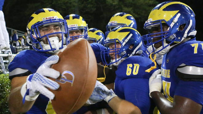 Delaware's Charles Scarff enjoys his touchdown reception with teammates including Peter Thistle (60) and Steve Robinson (right) in the third quarter of Delaware's 56-14 win at Delaware Stadium Thursday.