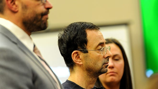 Larry Nassar, flanked by his attorneys, listens as his sentence is ready by Judge Rosemarie Aquilina on Wednesday, Jan. 24, 2018, in Lansing, Mich.