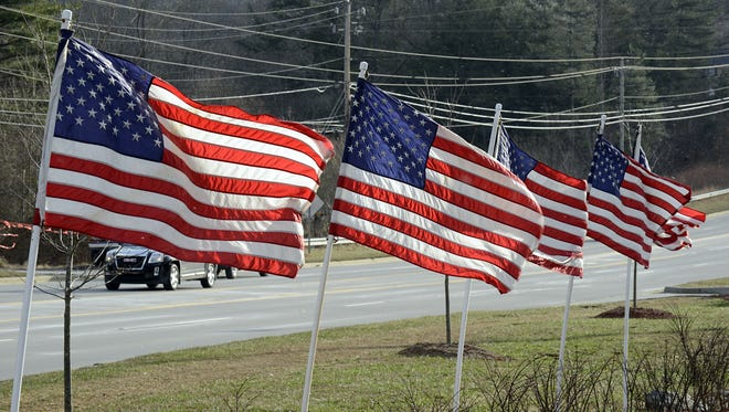 Wind lifts American flags in front of the Quality Plus gas station in Reynolds in this file photo. High winds are forecast for Thursday night and Friday.