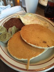 Three medium-sized pancakes, two eggs and a sausage