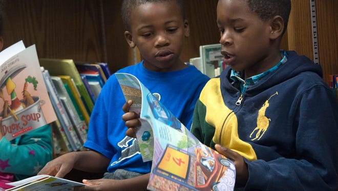 Ensley Elementary School first-graders, Kearien Brown, left, and JaquAvies Brye right, read from their new books.  The pair received the new books through a giveaway from Reading Is Fundamental Friday morning.