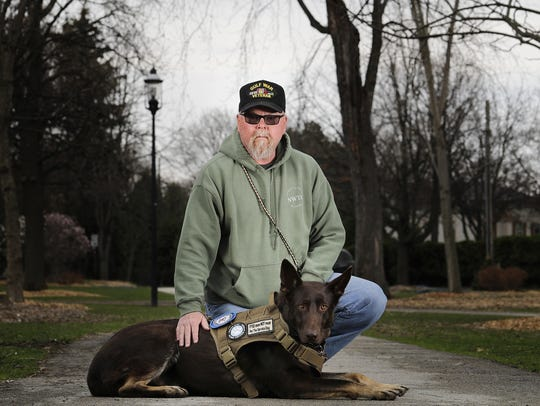 Gulf War veteran Warren Demmin of Sturgeon Bay kneels with Loki, his PTSD service dog in training at St. James Park in Green Bay. Demmin was paired with Loki through the White Paws German Shepherd rescue.