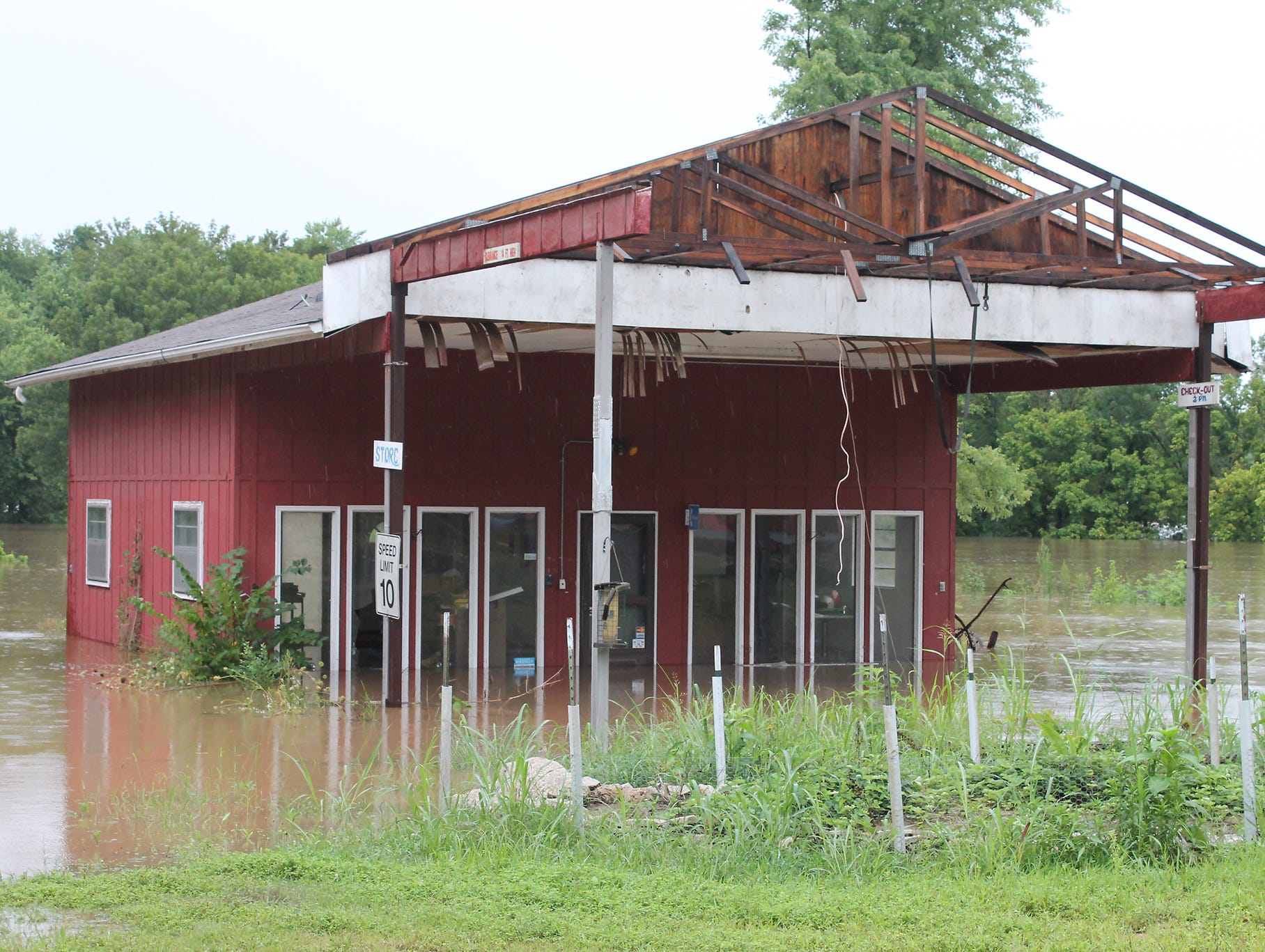 Floodwaters surround a former grocery store at a campground in Arlington.