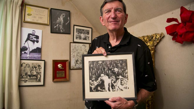 Randy Duncan in his attic holding a photo from an Iowa football game against Air Force.