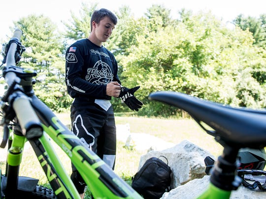 Ian Norris puts gloves on before riding at Codorus State Park. When he was 15, Norris became obsessed with downhill racing, calling it 'the gnarliest version of mountain biking.'