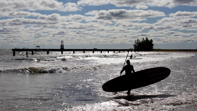 Water samples were taken from beaches along the coasts and the Great Lakes. Here, paddle boarders try to catch some waves on North Avenue Beach in  Lake Michigan, outside Chicago, July 24, 2013.
