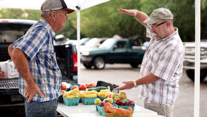 Perry Eubanks, left, and Ron Steckler of Salt Lake City talk about watermelons at the Downtown Hattiesburg Farmers Market. The farmers market operates in Town Square Park from 3 to 6 p.m. on Thursdays beginning this week.