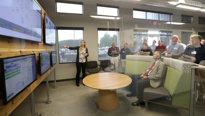 Caramy Biederman, left, of Faith Technologies, speaks to a tour group Thursday in the control room of the microgrid at Gordon Bubolz Nature Preserve.