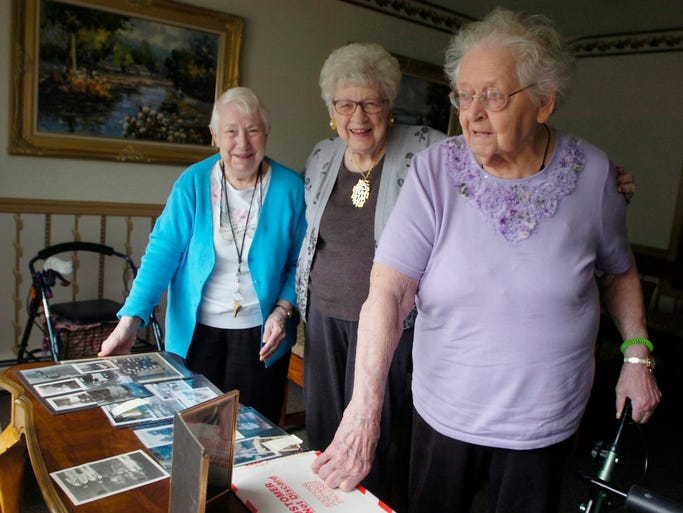 Recarda Moore (left), Jean Chappa and Mary Helen Penoza check out old photos from their personal albums. The women all live at American House in Farmington Hills and worked as riveters for the same company during World War II.