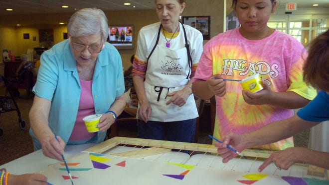 Cancer survivor Betty Cathey (left) paints as artist Wendy Starn (center) gives her some instruction while at the Cabrini Cancer Center for a past Arts and Healthcare event.
