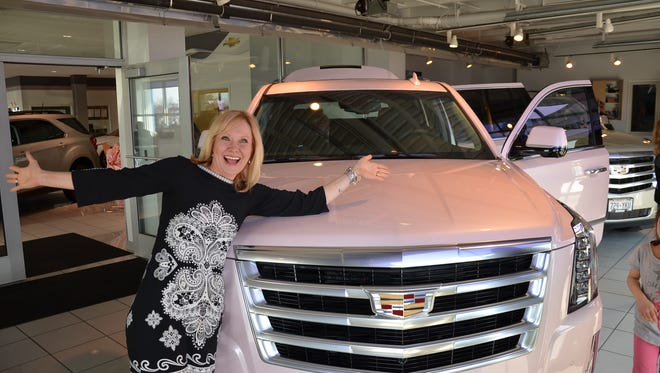 Heidi Goelzer poses with her newly awarded company car, a pearlized pink Cadillac Escalade. Goelzer works for May Kay.