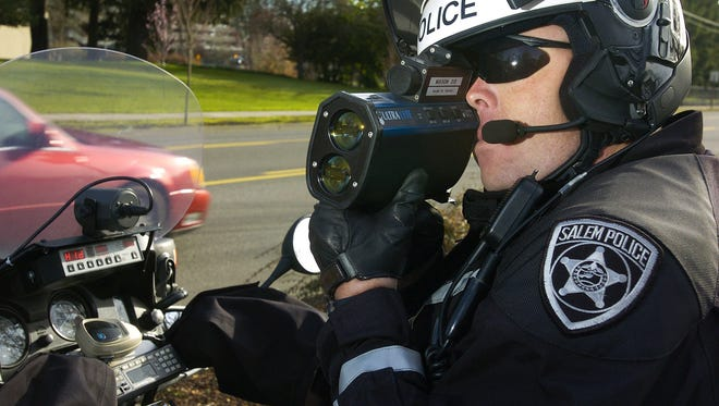 Mitch Mason, Salem traffic officer, uses a LIDAR speed gun to check for speeding drivers on March 3, 2006.