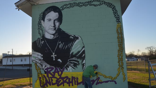 Mural artist Bryan Deese spray painted a chain bordering his newest creation Nov. 28 honoring professional skateboarder and Gallatin native Ray Underhill.