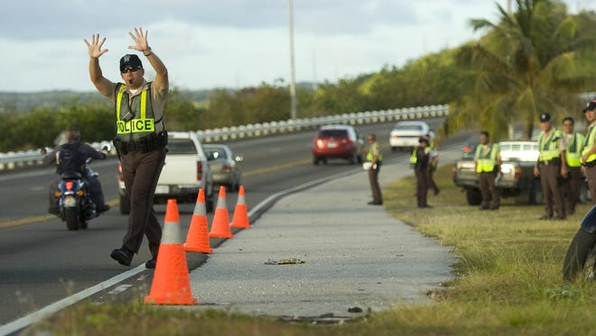 "In this May 2010, file photo Guam International Airport Authority Officer Dean Delgado, now a lieutenant, stops a motorist during ""Click It or Ticket"" enforcement duties on Route 10A."