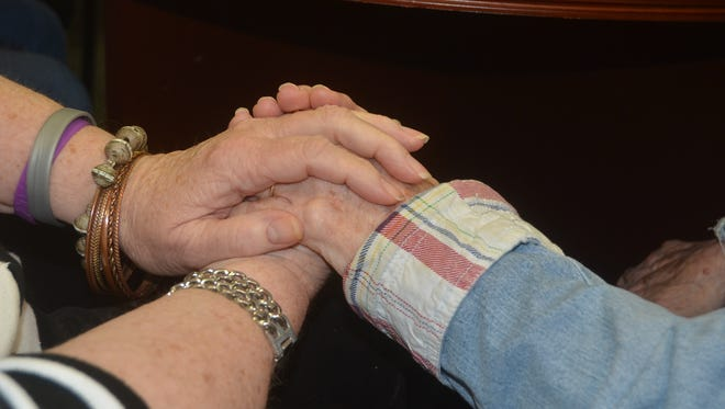 Jean McCaslend, who has Alzheimer's, often holds hands with her friends at The Veranda in Gallatin.