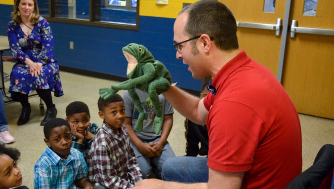 """Chadwick Gillenwater, or """"Professor Watermelon,"""" uses a frog puppet during one of his reading sessions at IPS School 43. Gillenwater provides read-aloud training to different local groups for Indy Learning."""