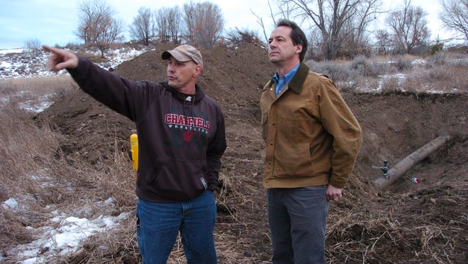 Paul Peronard, left, with the U.S. Environmental Protection Agency, describes a pipeline spill along the Yellowstone River near Glendive, Mont. as Gov. Steve Bullock listens, Monday, Jan. 19, 2015. Up to 50,000 gallons of oil were released.
