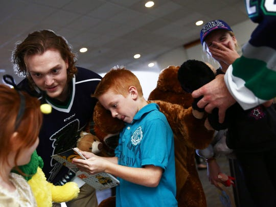 Florida Everblades player Tyler Ganly of Mississauga, Ontario gives stuffed animals to siblings, from left, Jade, 6, Titus, 8, and Alyssa Sabean, 11, at Golisano Children's Hospital of Southwest Florida on Monday, Dec. 14, 2015. The Florida Everblades ice hockey team delivered donated stuffed animals to patients at the hospital. (Dorothy Edwards/Staff)
