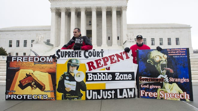 Pro-life demonstrators stand outside the Supreme Court after oral arguments in the case of McCullen v. Coakley, dealing with a Massachusetts law imposing a 35-foot buffer zone around abortion clinics for demonstrations and protests, on Jan. 15 in Washington, D.C.