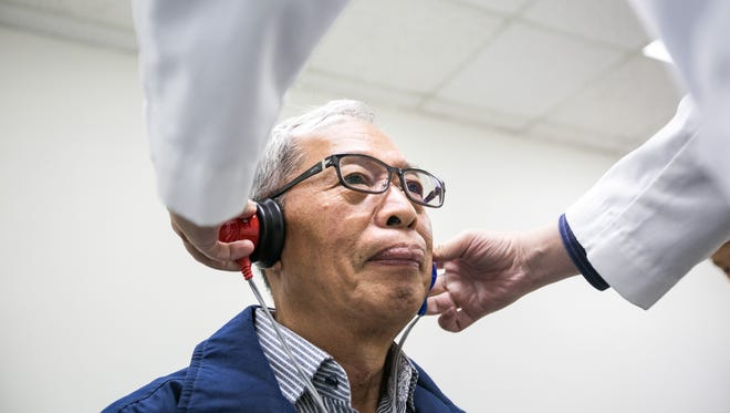 Doctor Ivan T.J. Wu, an audiologist, places headphones on Chin Yin Chiu's for a hearing test during the Hsi Lai Temple Health Fair, in Hacienda Heights, Calif., on May 10, 2015.