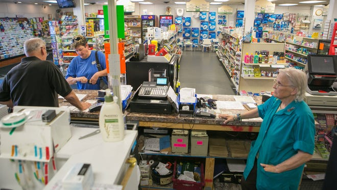 Manor Pharmacy clerks Kerry Hoopes (left) and Shirley Wiggins work the cashier counter.