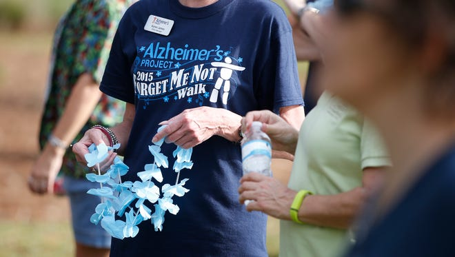 Participants at Cascades Park wear T-shirts and blue leis, a color and symbol for Alzheimer's awareness, during the 2015 Alzheimer's Project Forget Me Not Walk.
