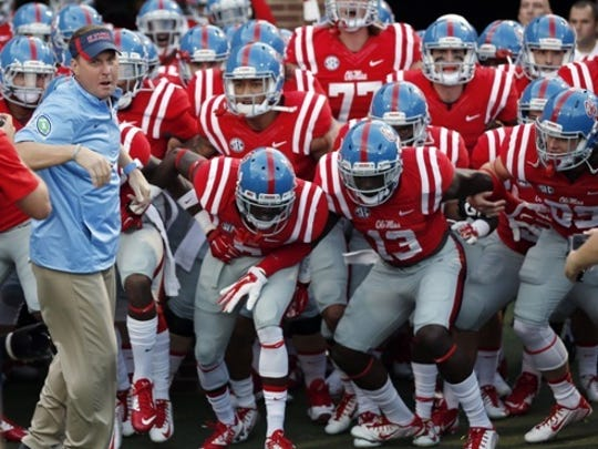 Mississippi coach Hugh Freeeze leads his team to the field for an NCAA college football game against Memphis in Oxford, Miss., Saturday, Sept. 27, 2014. (AP Photo/Rogelio V. Solis)