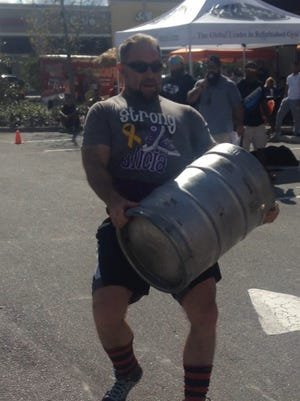 Dennis Walters lifts a beer keg during a previous strong man competition. Walters will not compete Saturday.
